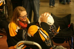 volunteer helps player in to their sled